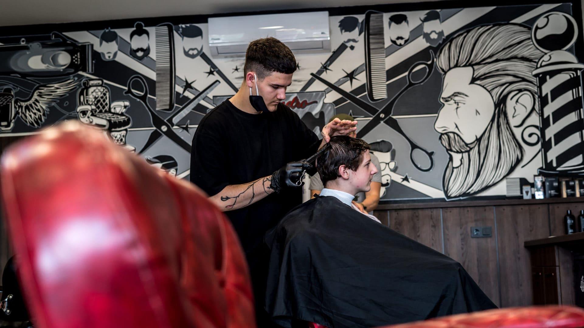 Holič Marco stříhá klienta